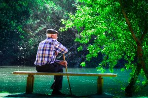 elderly man meditating on bench near lake