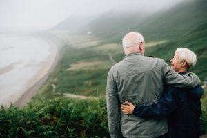 elderly couple gazing at beach and foliage